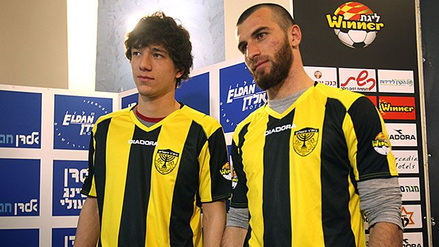 Chechen football players Dzhabrail Kadaev (L) and Zaur Sadaev, signed from Russian League club Terek Grozny, show off their new shirts during their introduction by the Beitar Jerusalem football club to the press in Jerusalem on January 30, 2013. Beitar Je