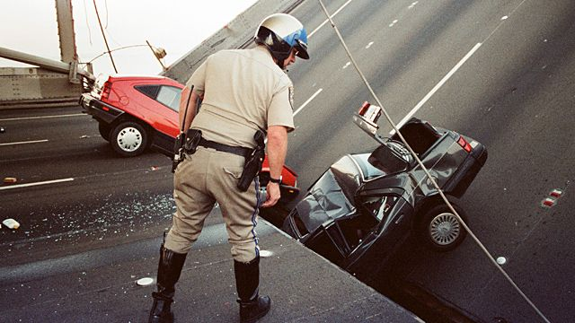 California Highway Patrol officer checks the damage to cars that fell when the upper deck of the Bay Bridge