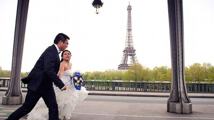 A bride and her husband walk in front of the Eiffel tower