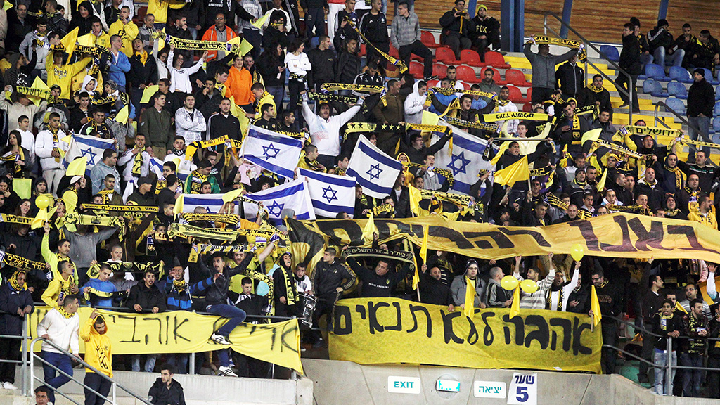 Beitar Jerusalem's supporters chant slogans beside a banner during an Israeli championship football match between Beitar Jerusalem and Bnei Sakhnin at the Teddy Kollek Stadium in Jerusalem on February 10, 2013.