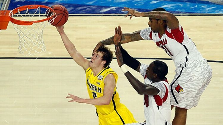 Spike Albrecht #2 of the Michigan Wolverines drives for a shot attempt against Gorgui Dieng #10 and Chane Behanan #21 of the Louisville Cardinals during the 2013 NCAA Men's Final Four Championship at the Georgia Dome on April 8, 2013 in Atlanta, Georgia.