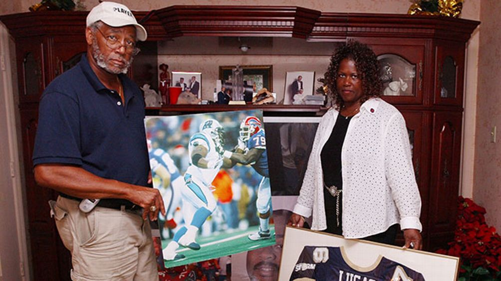David Lucas holds a picture of his son, Al Lucas, taken during Al's time with the Carolina Panthers, as Elaine Lucas, right, holds Al's jersey that he wore with the Arena Football League's Tampa Bay Storm, Thursday, Aug. 18, 2005. Al was killed in an Aren