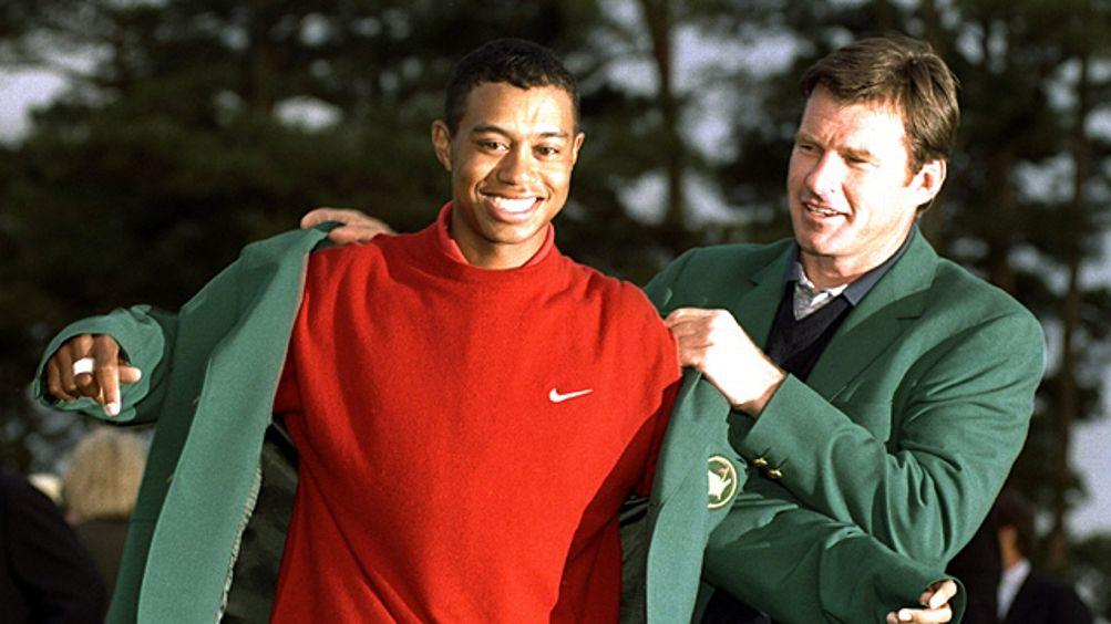 1996 US Masters winner Nick Faldo of Great Britain helps 1997 winner Tiger Woods