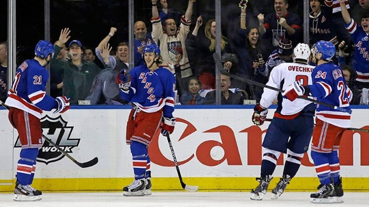 New York Rangers left wing Carl Hagelin (62), of Sweden, and right wing Ryan Callahan (24) celebrate with center Derek Stepan (21) after Stepan scored a goal as Washington Capitals left wing Alex Ovechkin (8), of Russia, skates past them in the third peri