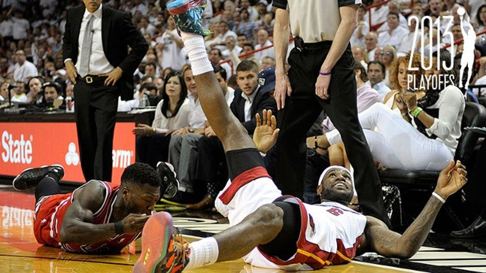 Miami Heat forward LeBron James looks up for the ball after diving on the floor next to Chicago Bulls guard Nate Robinson during the second quarter in the NBA Eastern Conference playoffs at the AmericanAirlines Arena in Miami, Florida, Monday, May 6, 2013