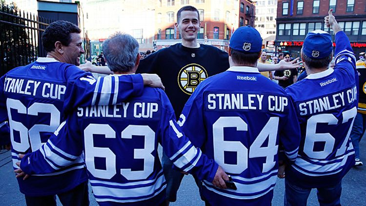 A Boston Bruins fan and a group of Toronto Maple Leafs fans
