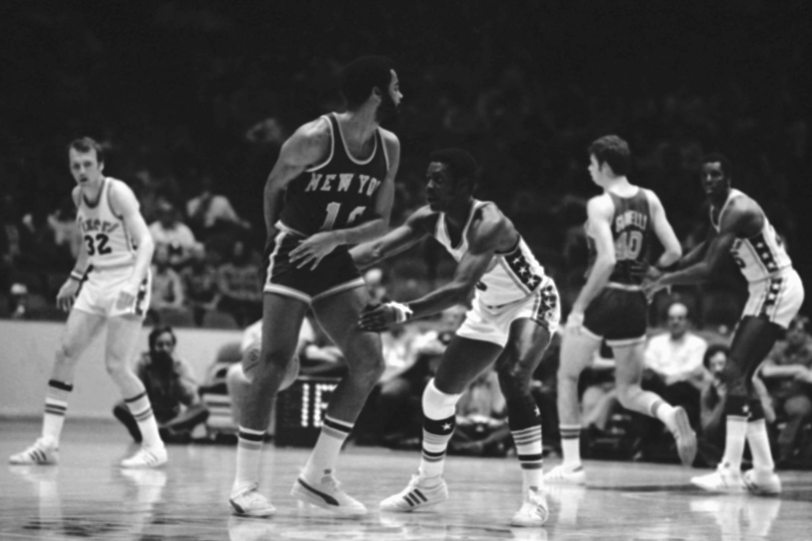 Philadelphia 76ers guard Fred Carter (3) reaches for the ball, but New York Knicks guard Walt Frazier (10) flicks it behind his back to a teammate in the first quarter of an NBA game in Philadelphia on Wednesday, Nov. 20, 1974.