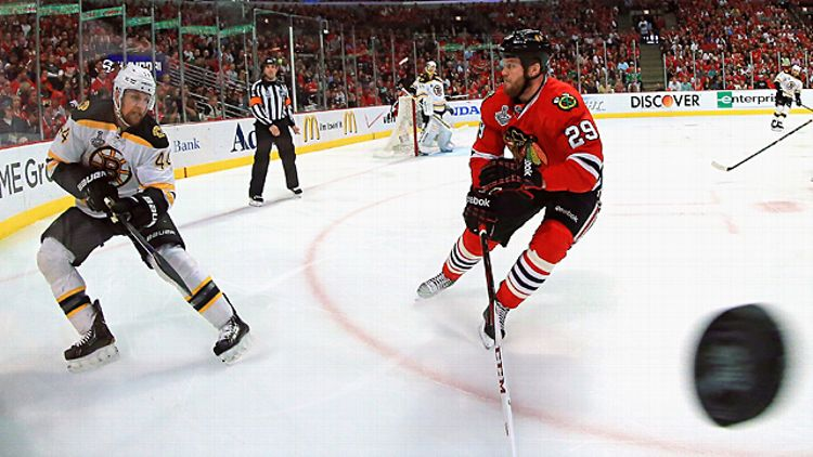 Dennis Seidenberg #44 of the Boston Bruins shoots the puck past Bryan Bickell #29 of the Chicago Blackhawks