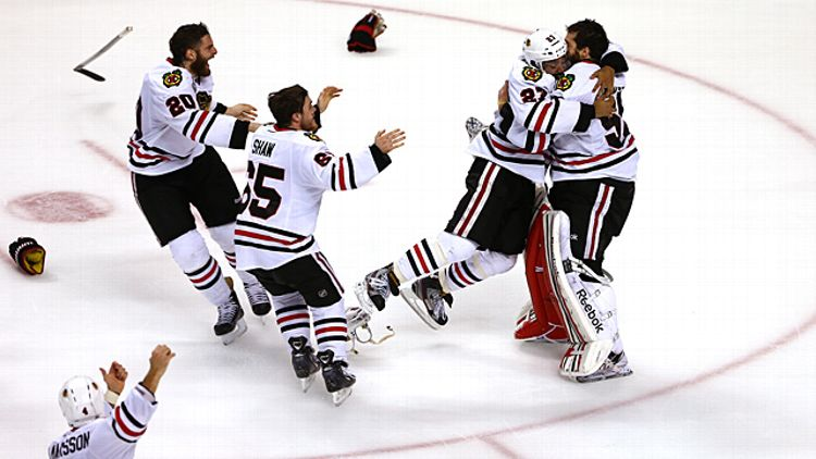 Johnny Oduya #27 of the Chicago Blackhawks celebrates with Corey Crawford #50
