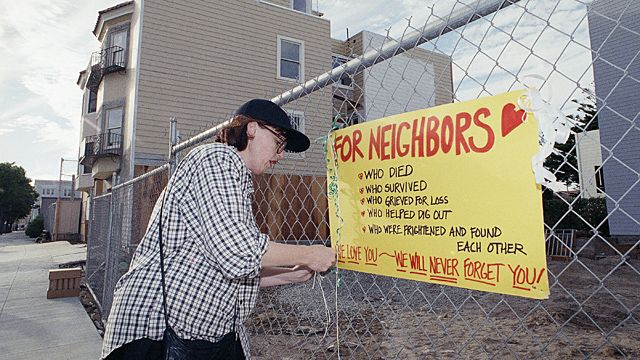 Deanna Del Bridge hangs a sign on a fence which expresses her love for her neighbors in San Francisco?s Marina District