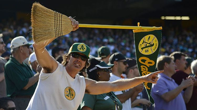 An Oakland Athletics fan holds up a broom for the series sweep against the Texas Rangers at O.co Coliseum on October 3, 2012 in Oakland, California. The Athletics won the game 12-5 capturing the American League West title.