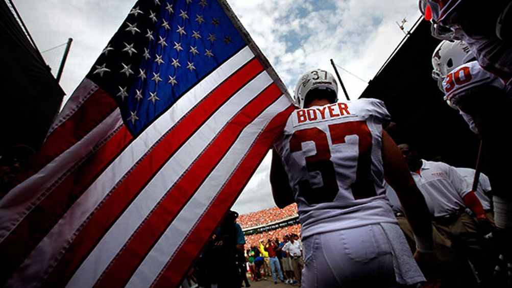Nate Boyer #37 of the Texas Longhorns carries an American flag as the Texas Longhorns take to the field against the Oklahoma Sooners at Cotton Bowl on October 13, 2012 in Dallas, Texas.