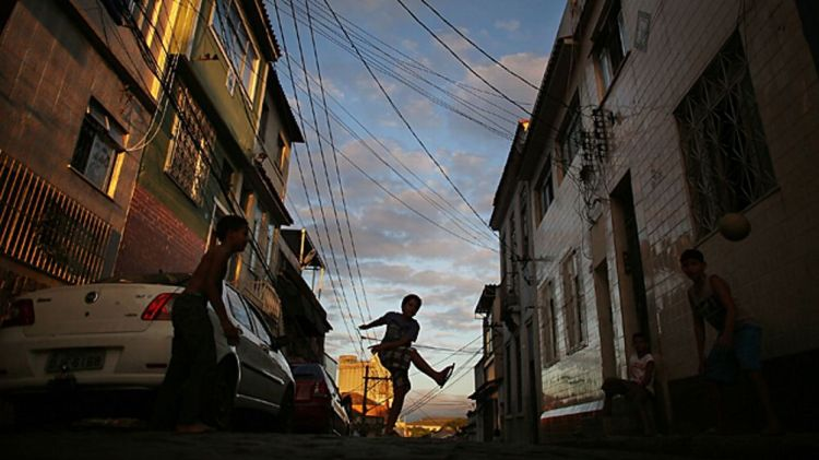 Boys play football in the street