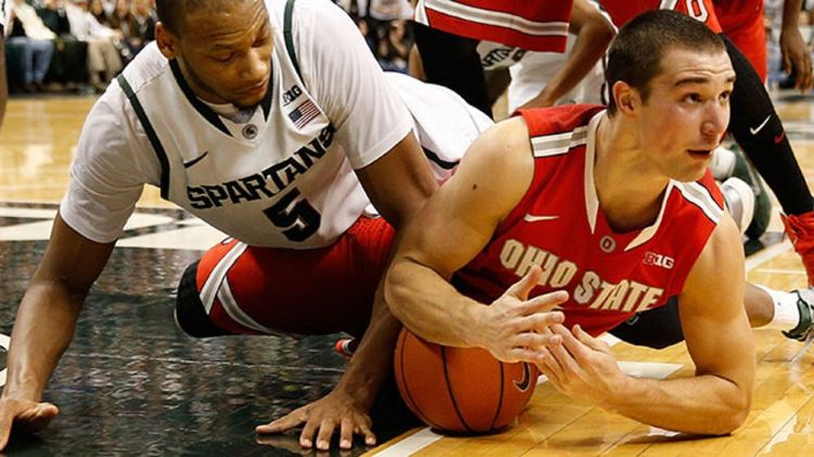 Aaron Craft #4 of the Ohio State Buckeyes calls a second half timeout after diving for the ball next to Adreian Payne #5 of the Michigan State Spartans at the Jack T. Breslin Student Events Center on January 7, 2014 in East Lansing, Michigan. Michigan Sta