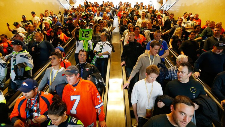 Football fans make their way to trains on Sunday, Feb. 2, 2014, in Secaucus, N.J. The Seattle Seahawks are scheduled to play the Denver Broncos in NFL football's Super Bowl XLVIII game on Sunday evening at MetLife Stadium in East Rutherford, N.J.