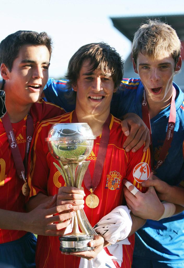 Spain's Bojan Krkic (C) holds the trophy