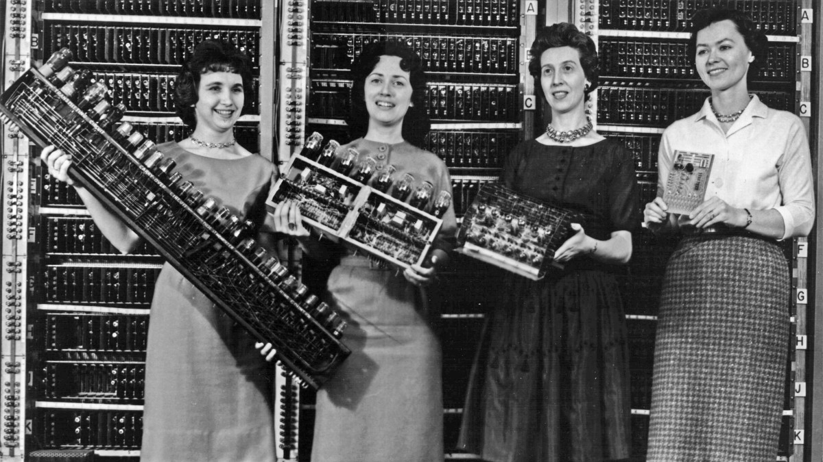 Left: Patsy Simmers, holding ENIAC board. Next: Mrs. Gail Taylor, holding EDVAC board. Next: Mrs. Milly Beck, holding ORDVAC board. Right: Mrs. Norma Stec, holding BRLESC-I board.