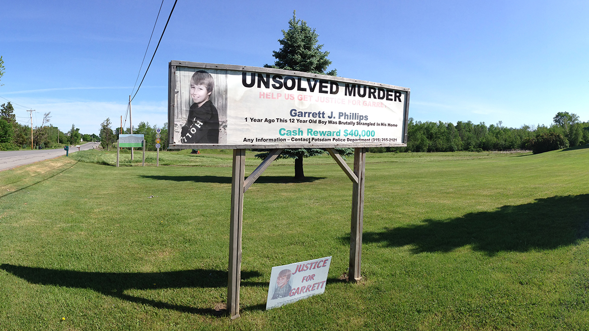 A Potsdam lawn sign calling for tips to help solve the case of Garrett's killing.