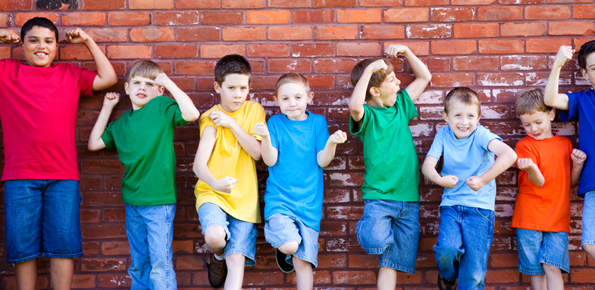 boys-flexing-muscles-by-brick-wall-Image