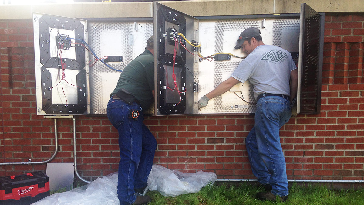 Adam (right) and a fellow electrician install a clock at Durham Bulls Athletic Park. (Adam Sobsey)