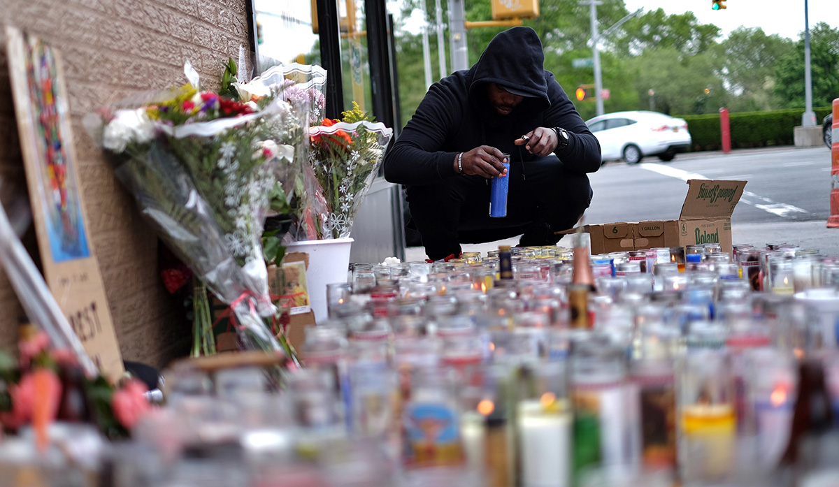 A mourner lights a candle on May 18, 2105 at a makeshift memorial beside a street in Queens, New York, where rapper Chinx was shot dead.