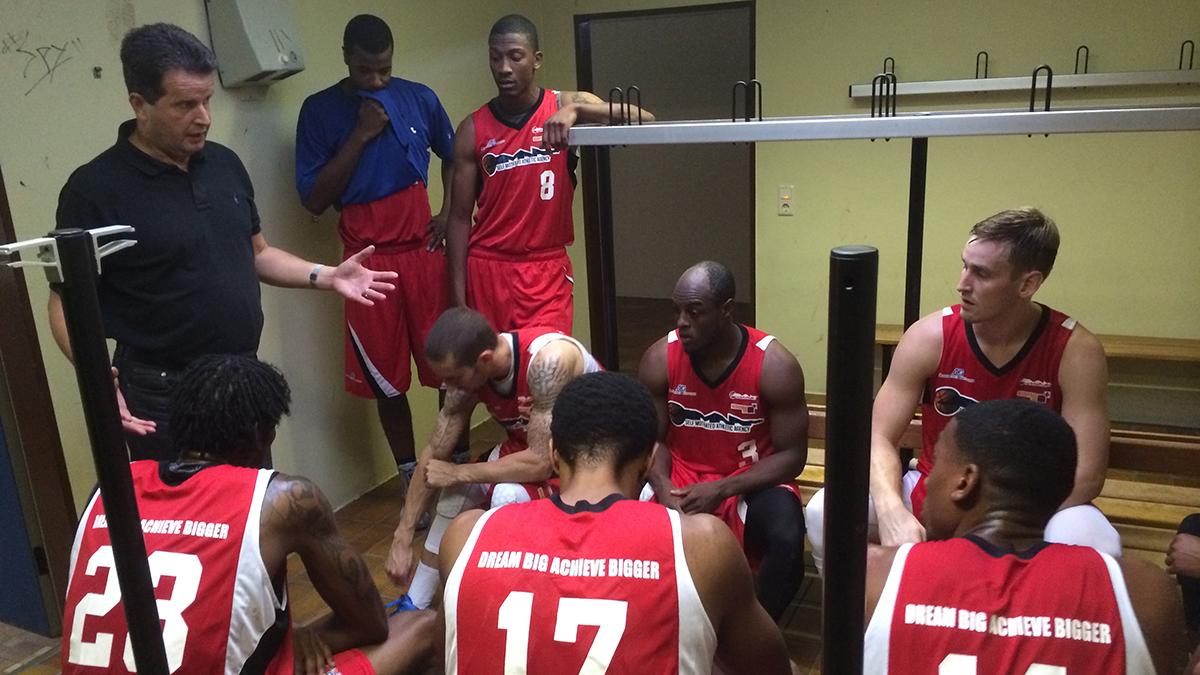 Coach Hans Beth addresses the SMAA team in a locker room in Heidelberg.