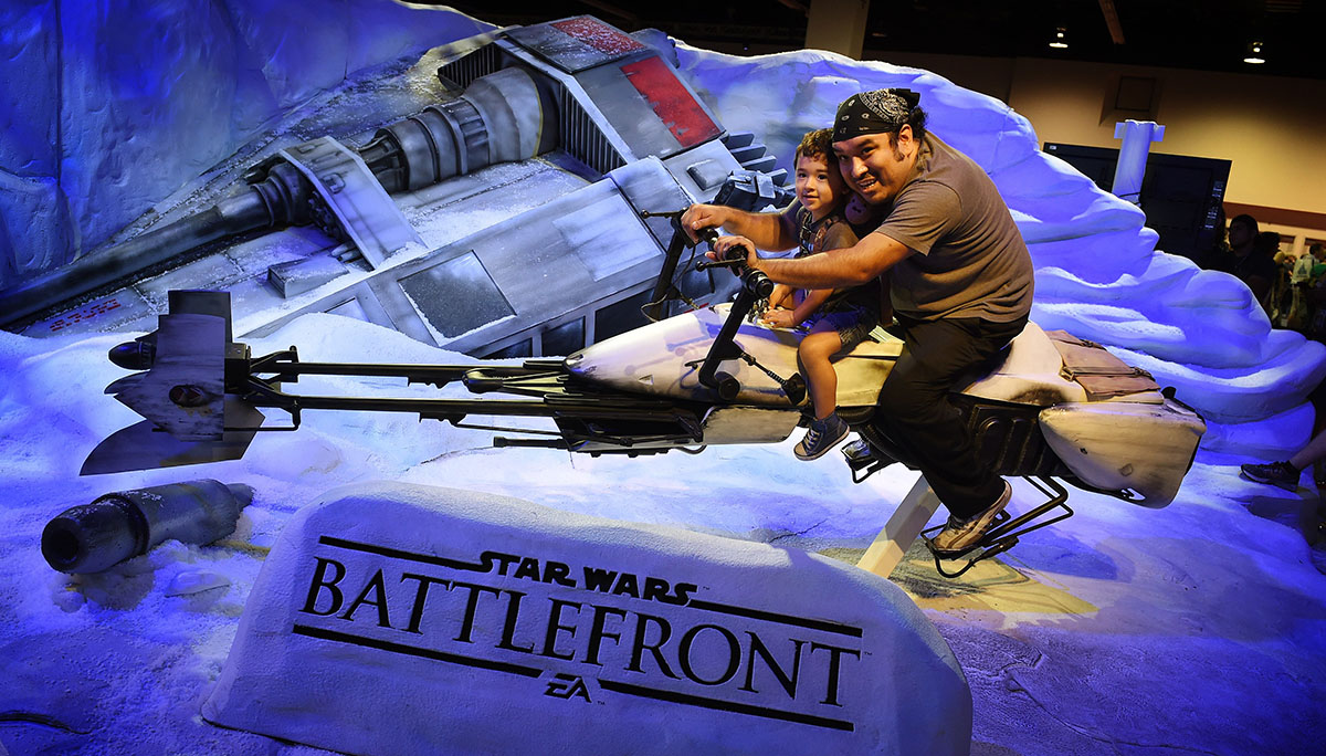 Star Wars fans Maico Santos and his son Julian ride a Star Wars display during the Disney D23 EXPO 2015 on Sunday.