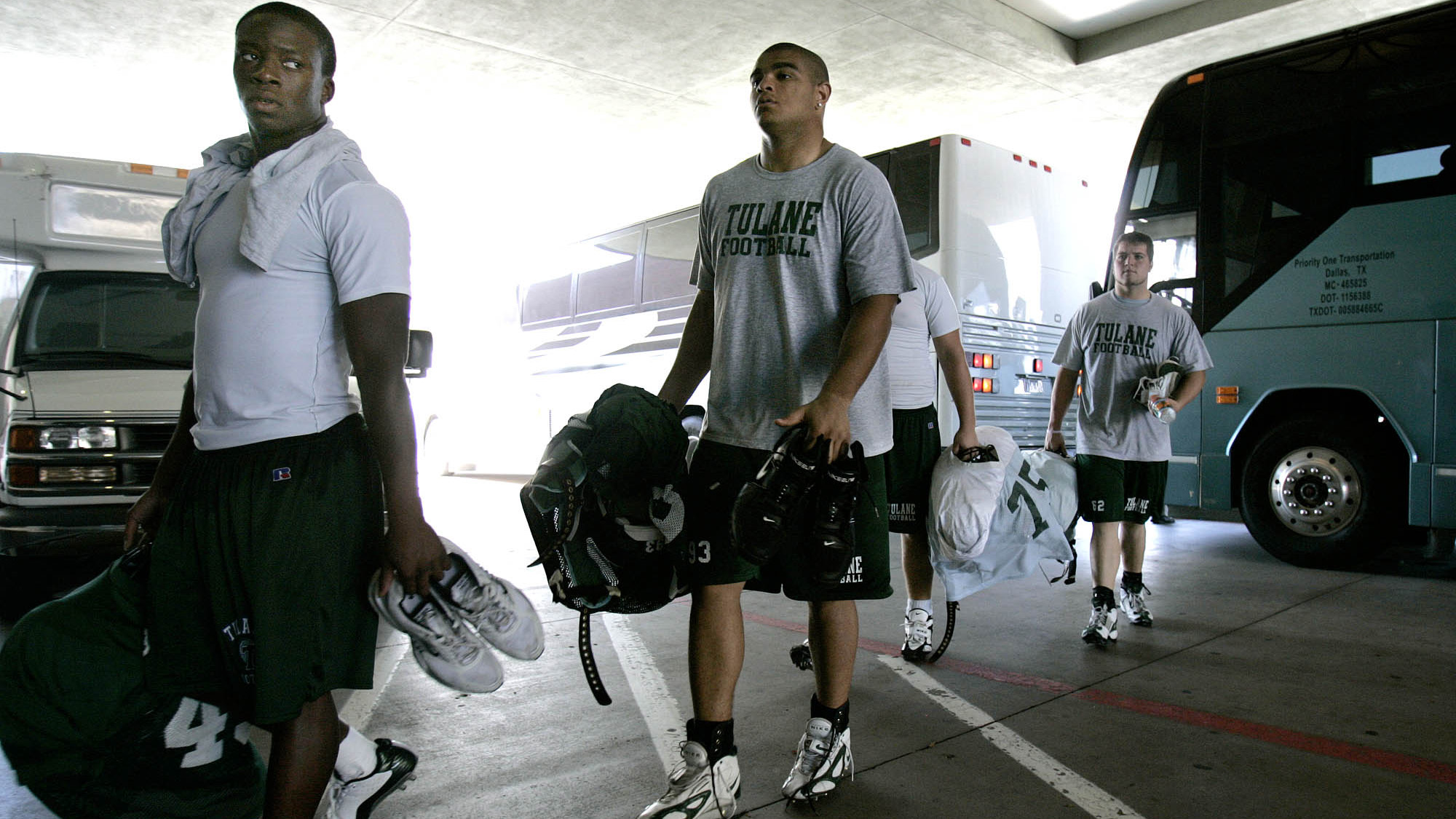 Tulane football players Christian Okoye, left, Taurean Brown, center, and Chris Bordelon, right, arrive at the Doubletree Hotel after a team practice in Dallas, Tuesday, Sept. 5, 2005.